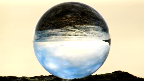 vidéos et rushes de boule de verre sur rocher devant les vagues de la mer - ball