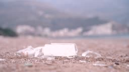 Glass bottle with a manuscript inside falls from above on the pebble beach on sea coast and broken. Roll of paper with message became visible. Concept of adventures or travels. Outdoors.