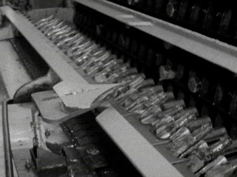 vídeos de stock, filmes e b-roll de glass bottles are tipped over as they move along an automated production line at the schweppes factory - 1960