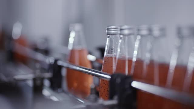 stockvideo's en b-roll-footage met de flessen van het glas bewegen zich langs een transportband - verfrissing