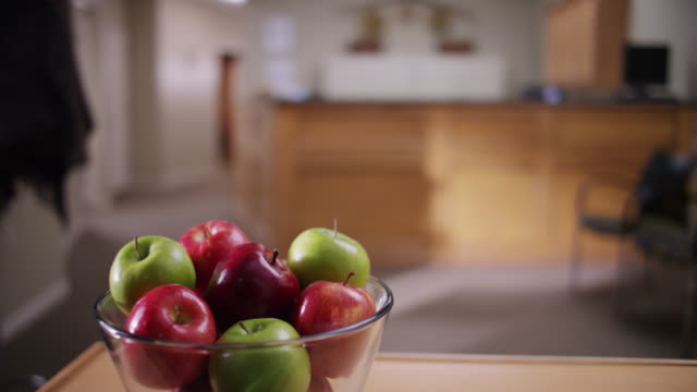 vidéos et rushes de glass bowl filled with red and green apples sits on a table. - coupe à fruits