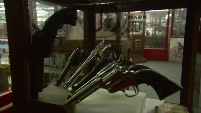 a glass case displays a collection of handguns. - skåp med glasdörrar bildbanksvideor och videomaterial från bakom kulisserna