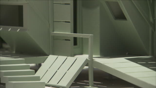 a glass case holds a miniature model of a house with odd angles. - 陳列ケース点の映像素材/bロール