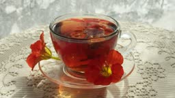 Glass cup of hot herbal tea and red nasturtiums