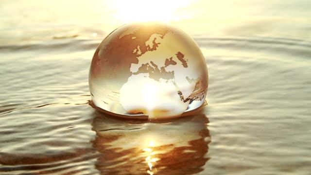 vídeos y material grabado en eventos de stock de globo de tierra de cristal spinning at seaside - mapa mundial