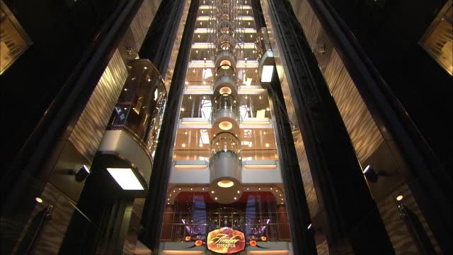 A glass elevator ascends through an atrium.