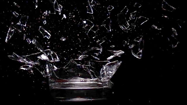 vídeos de stock, filmes e b-roll de ms slo mo glass exploding against black background / vieux pont, normandy, france  - copo