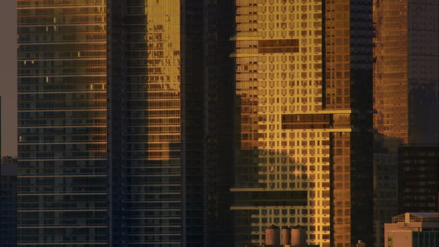 glass exteriors of new york city skyscrapers reflect soft early morning light. - campo totale video stock e b–roll