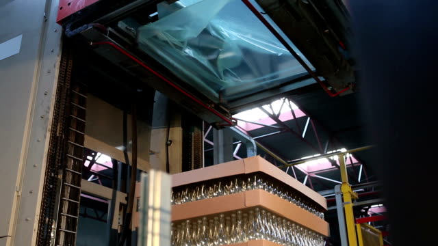 glass factory. packing bottles with cellophane. - crate stock videos & royalty-free footage
