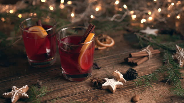 glass filled with mulled wine with oranges and cinnamon, surrounded by fir branches and spices - sweet food stock videos & royalty-free footage