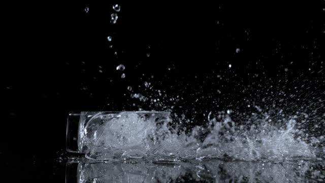 slo mo ld glass full of water hitting the surface and shattering - drinking glass stock videos & royalty-free footage