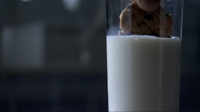 vídeos y material grabado en eventos de stock de glass full of white milk, unidentifiable male hand reaching off-camera, grabbing cookie & dipping cookie into glass of milk, taking cookie out of... - mojar