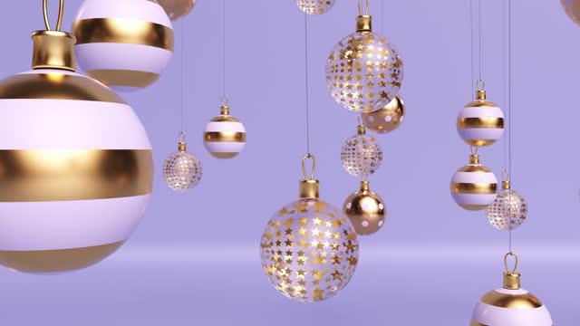glas gold und weiße weihnachtskugeln auf dünnen fäden auf einem hellvioletten hintergrund aufgehängt - kugelform stock-videos und b-roll-filmmaterial