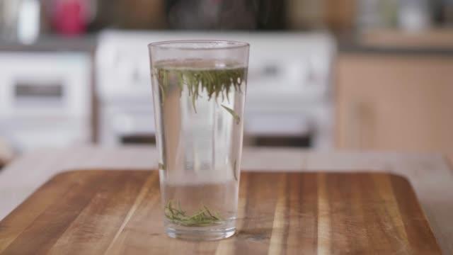 Glasgrüner Tee auf Holzbrett