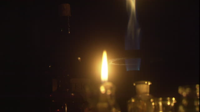 glass jars and vials surround a burning candle and bunsen burner. - bunsen burner stock videos & royalty-free footage