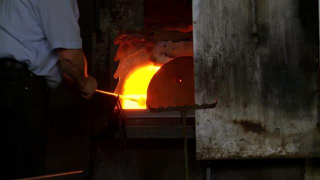 vídeos de stock, filmes e b-roll de máquina de virar vidro derretido na fornalha ms - fundir técnica de vídeo