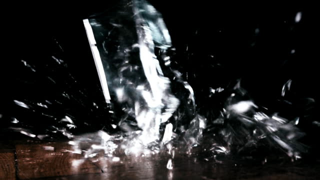 a glass object drops to the floor and shatters into pieces - destruction stock videos & royalty-free footage