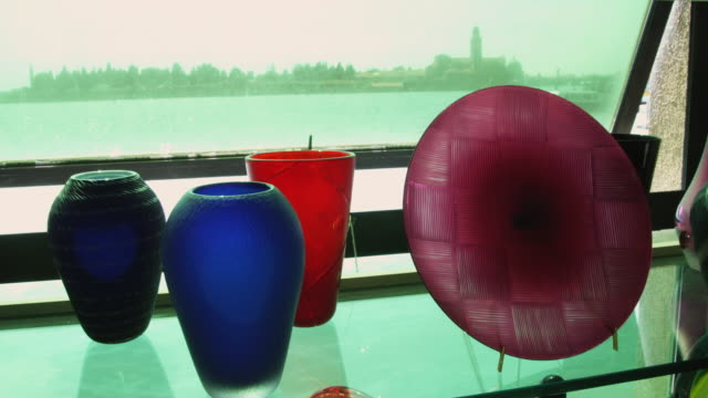 vídeos de stock e filmes b-roll de ms glass objects on display with boats on water in background / venice, italy - quatro objetos