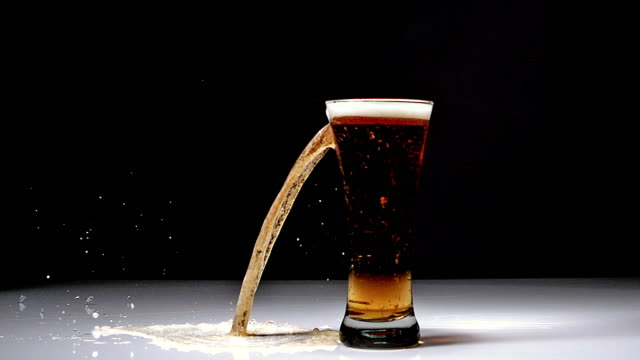 ms slo mo glass of beer breaking and splashing against black background / vieux pont, normandy, france - empty beer glass stock videos and b-roll footage