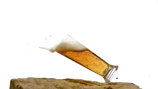 glass of beer falling and splashing on stone against white background, slow motion - empty beer glass stock videos and b-roll footage