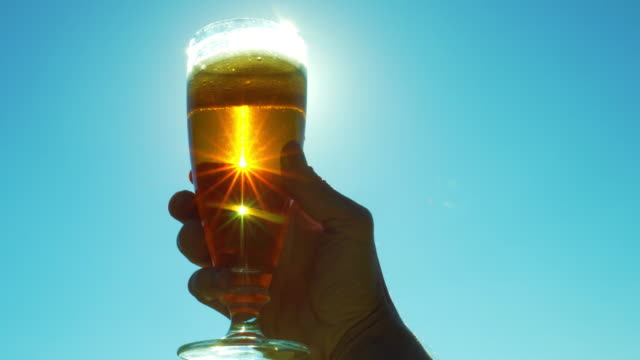 a glass of beer in hand against the sky in the sun - beer glass stock videos & royalty-free footage