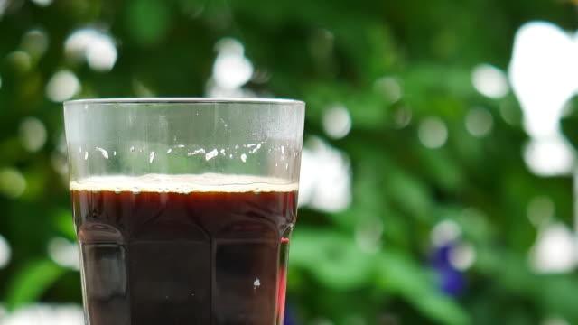 vidéos et rushes de verre de café chaud noir de fumée sur fond de nature. - tasse