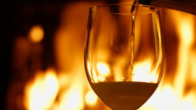 vídeos de stock e filmes b-roll de copo de champanhe sobre o fundo de fogo na lareira - lareira
