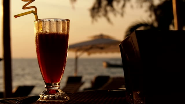 Glass of juice or cocktail on the beach