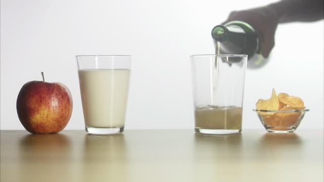 vídeos de stock, filmes e b-roll de a glass of milk and beer. - snack salgado