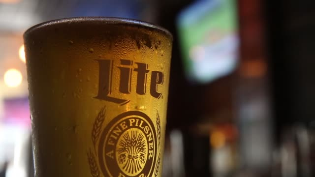 a glass of miller high life beer sits at a bar on october 9 2015 in new york city budweiser's parent company ab inbev is attempting to buy sabmiller - anheuser busch inbev stock videos and b-roll footage