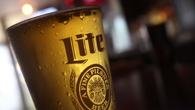 vídeos y material grabado en eventos de stock de a glass of miller high life beer sits at a bar on october 9 2015 in new york city budweiser's parent company ab inbev is attempting to buy sabmiller - anheuser busch inbev