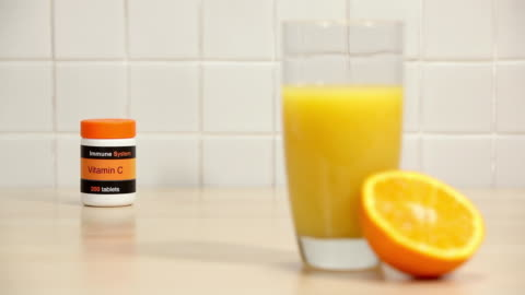 glass of orange juice and half an orange with vitamin c tablets - small group of objects stock videos & royalty-free footage