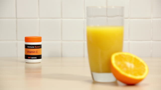 glass of orange juice and half an orange with vitamin c tablets - vitamin c stock videos and b-roll footage