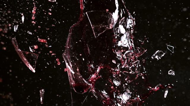 CU SLO MO Glass of red wine breaking and splashing / Vieux, Normandy, France