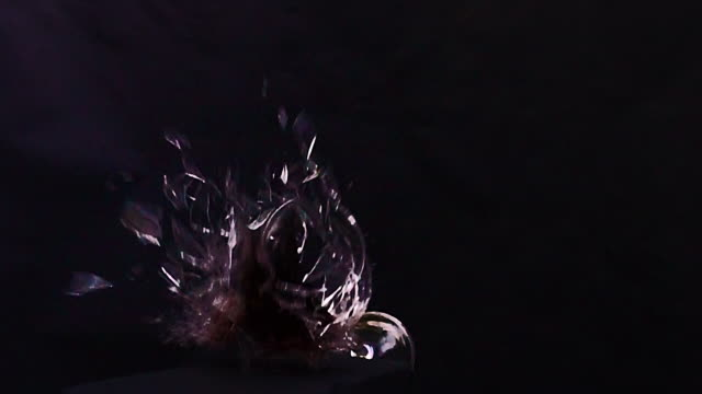 A glass of red wine drops and smashes in slow motion as the camera revolves around the action.