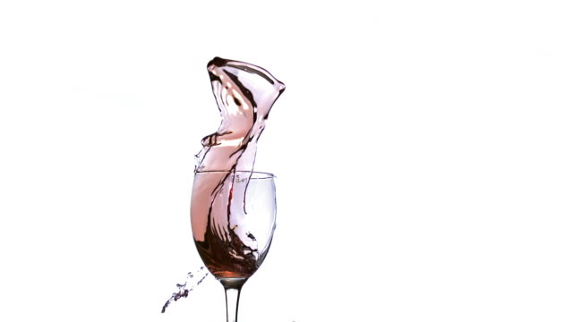 Glass of Red Wine Splashing against White Background, Slow motion