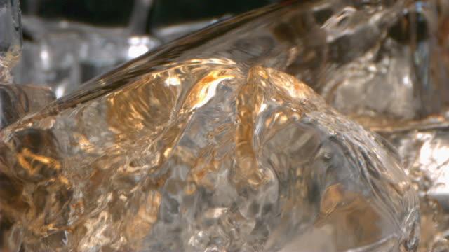 glass of splashing whiskey with ice in slow motion - アイスティー点の映像素材/bロール