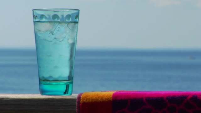 cu, glass of water and towel on wooden railing, ocean in background, north truro, massachusetts, usa - two objects stock videos & royalty-free footage