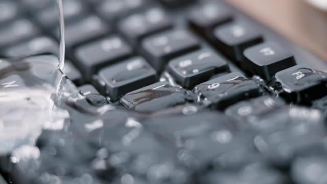 SLO MO LD glas water vallen op een zwart toetsenbord en het morsen van water op de toetsen