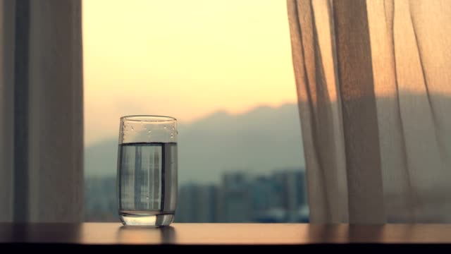 glass of water on table at sunset - still life stock videos & royalty-free footage