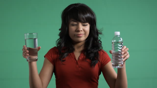 glass of water vs. bottled water - one teenage girl only stock videos & royalty-free footage