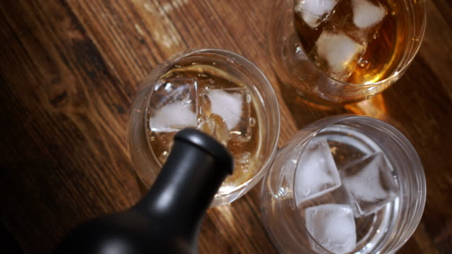 glass of whiskey with ice cubes and bottle on wooden table and against wooden background - scotch whiskey stock videos and b-roll footage