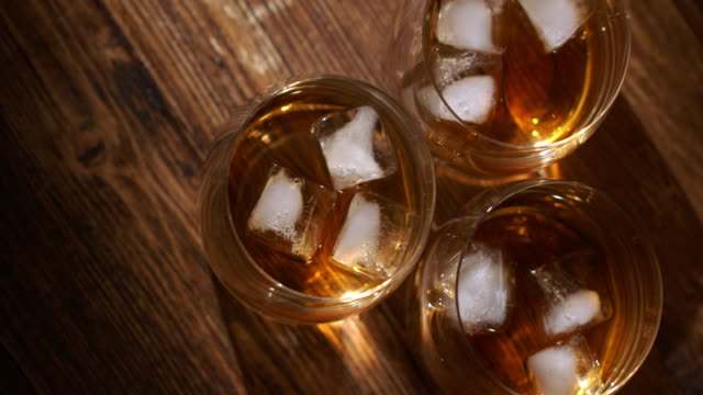 glass of whiskey with ice cubes and bottle on wooden table and against wooden background - cube stock videos & royalty-free footage