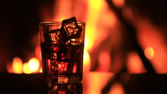 glass of whiskey with ice near the fireplace - scotch whiskey stock videos & royalty-free footage