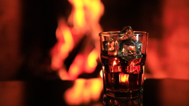 glass of whiskey with ice near the fireplace - destillation stock-videos und b-roll-filmmaterial