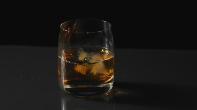glass of whiskey with ice on black background - scotch whiskey stock videos & royalty-free footage