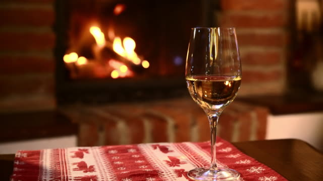 DS Glass of white wine by the fireplace