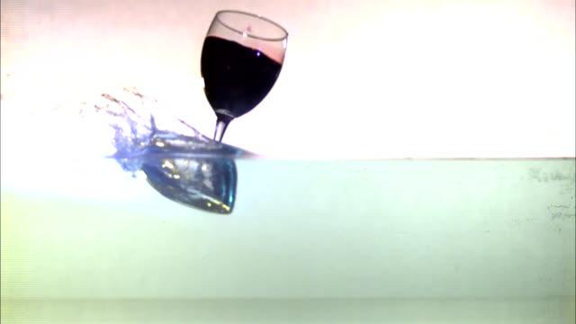 vídeos de stock, filmes e b-roll de a glass of wine falls into a layer of water and splashes. - tensão de superfície