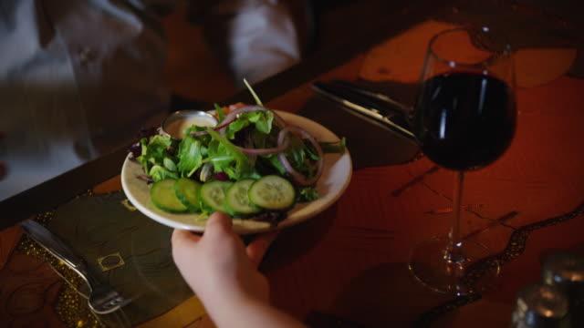 glass of wine on a restaurant table, a toss salad is served on a plate and a man's hands pick up silverware to begin eating. - servitris bildbanksvideor och videomaterial från bakom kulisserna