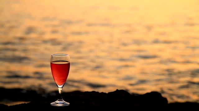 vídeos y material grabado en eventos de stock de dolly hd: copa de vino en la playa al atardecer - back lit